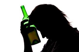Silhouette of sad man drinking alcohol